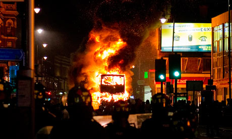 Firemen emerging from the shadows facing a vehicle on fire during London, England Riots in August 2011